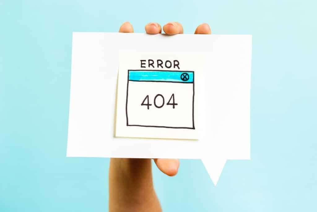 Hand holding a 404 error on a piece of paper