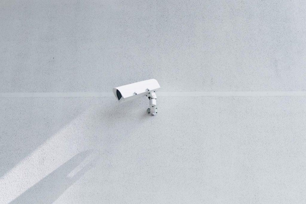 A white surveillance camera casts a shadow on a blank white wall