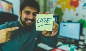 Man holding a post-it note with the word code